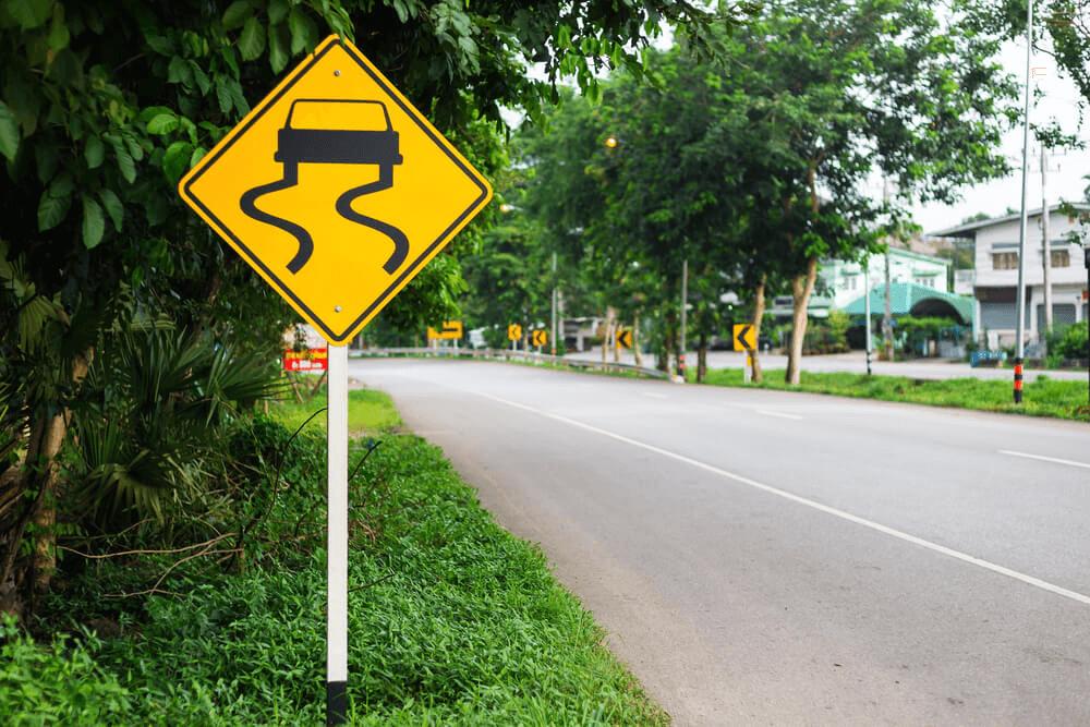 Slipperly warning sign road